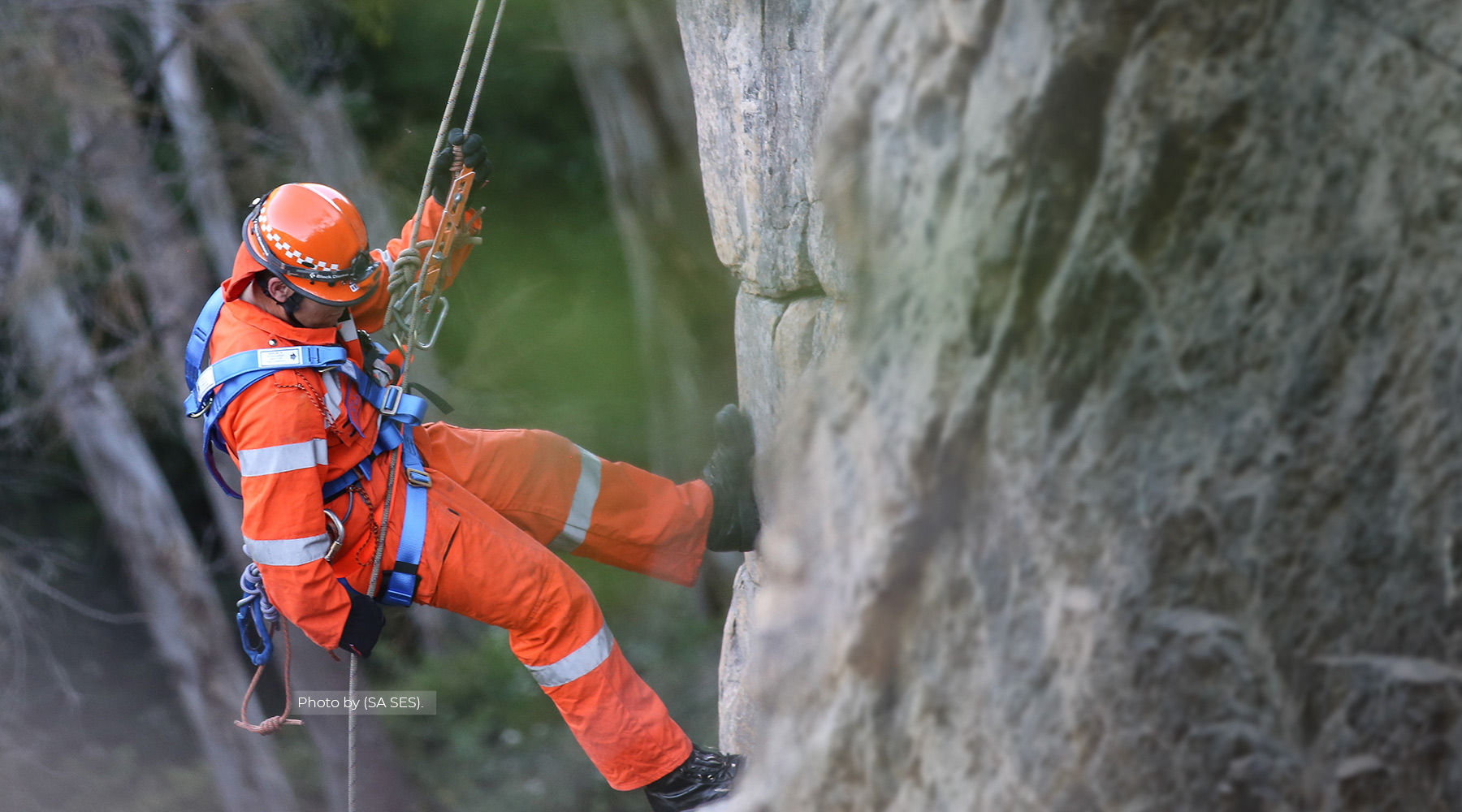 Man in orange uniform climbing a mountain
